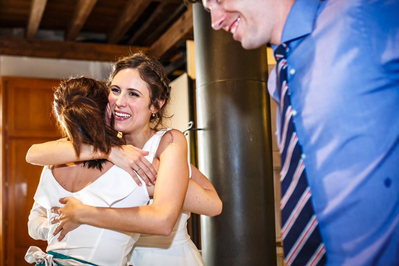 la novia abraza a una amiga tras darle los muñecos de la tarta en una boda en soria
