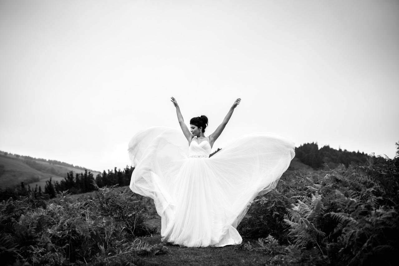 la novia lanza la cola de sus vestido en una postboda en peñas de aia