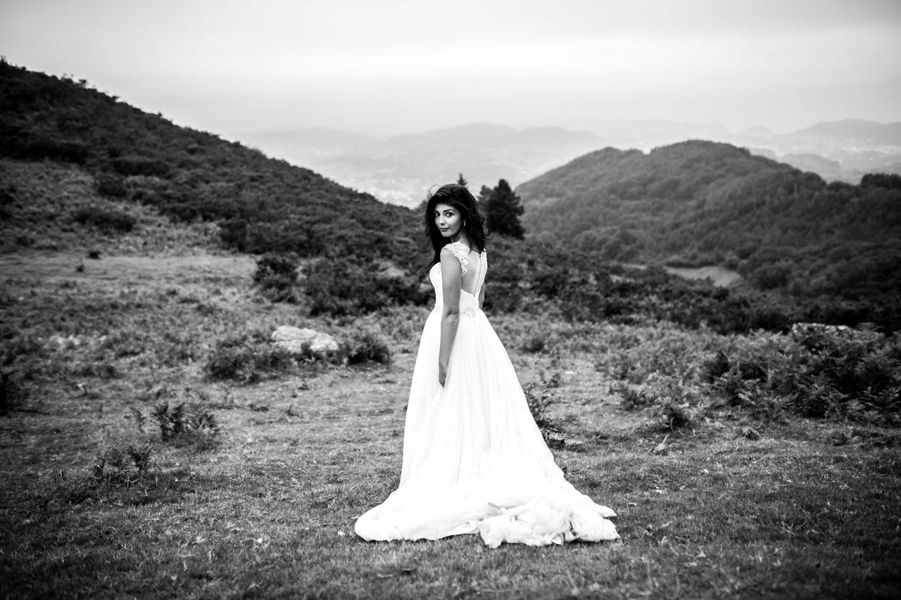 la novia mira a la cámara mientras camina en una postboda en peñas de aia