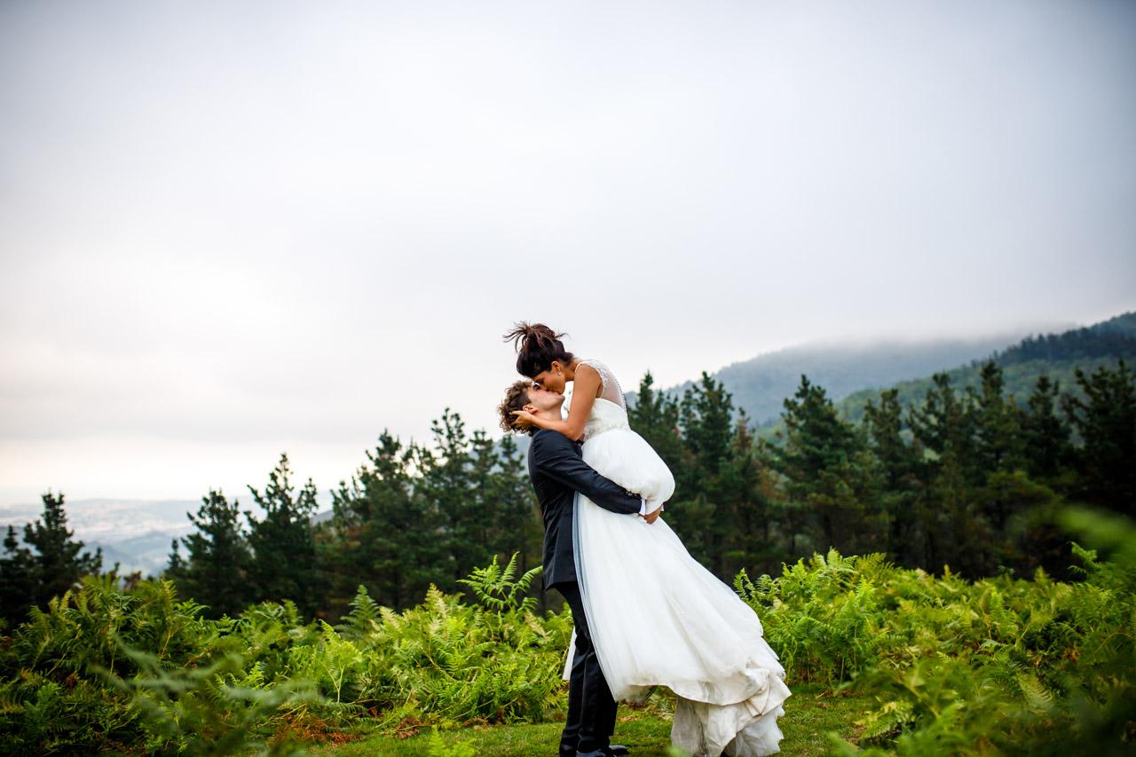 Los novios se besan mientras el la levanta en una postboda en peñas de aia