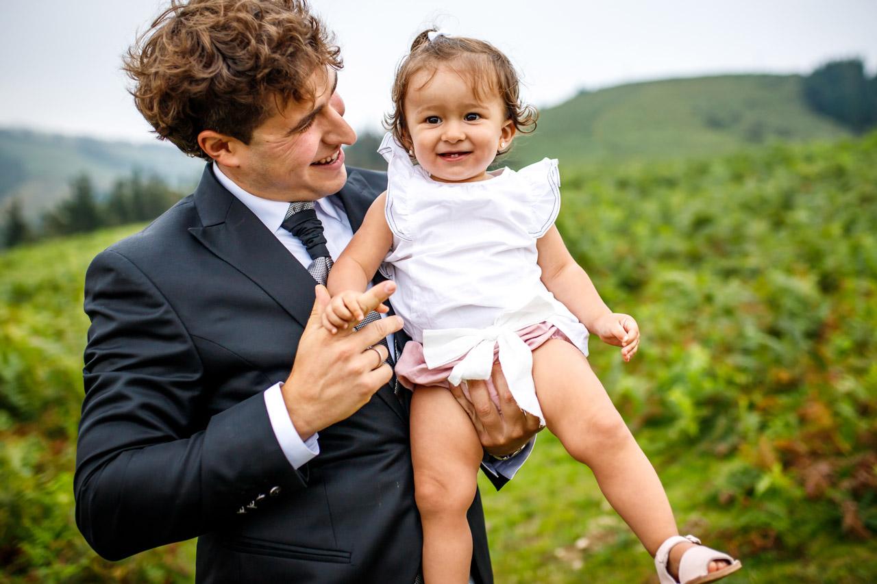 El novio sonríe con su hija en brazos en una postboda en peñas de aia