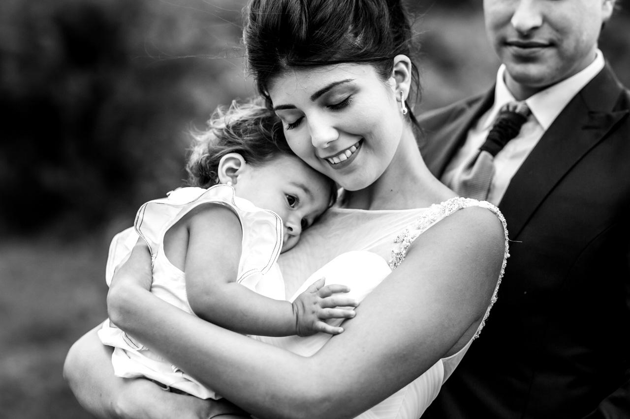 el novio mira a la novia abrazando a su hija en una postboda en peñas de aia