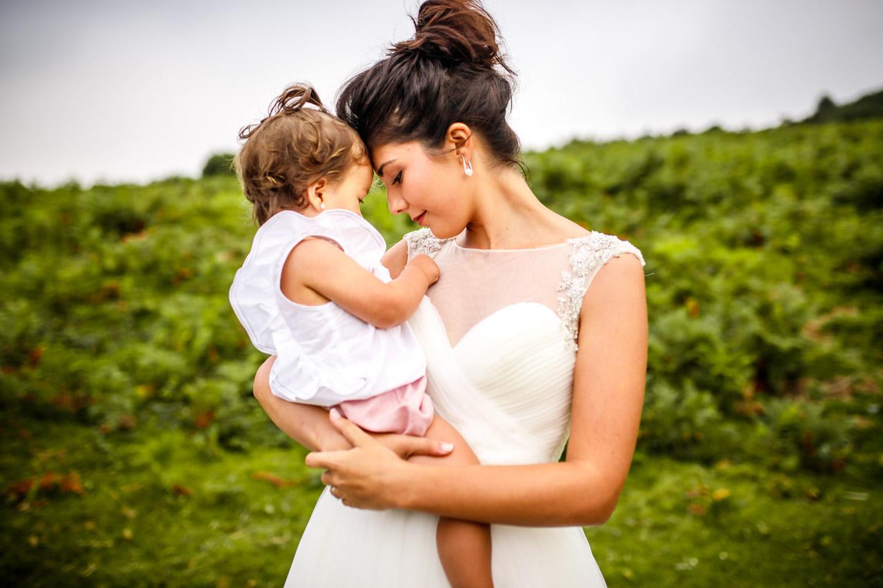 la novia con su hija en brazos en una postboda en peñas de aia
